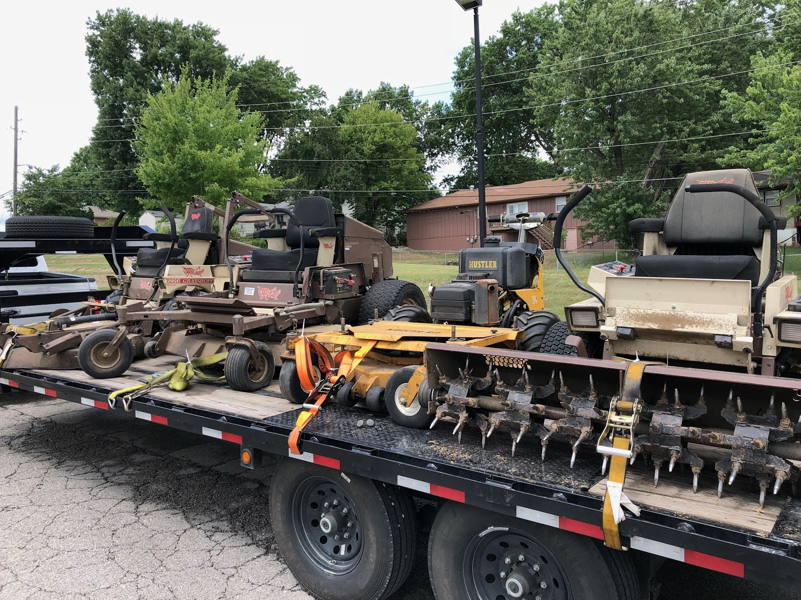 four zero turn riding lawn mowers being transported
